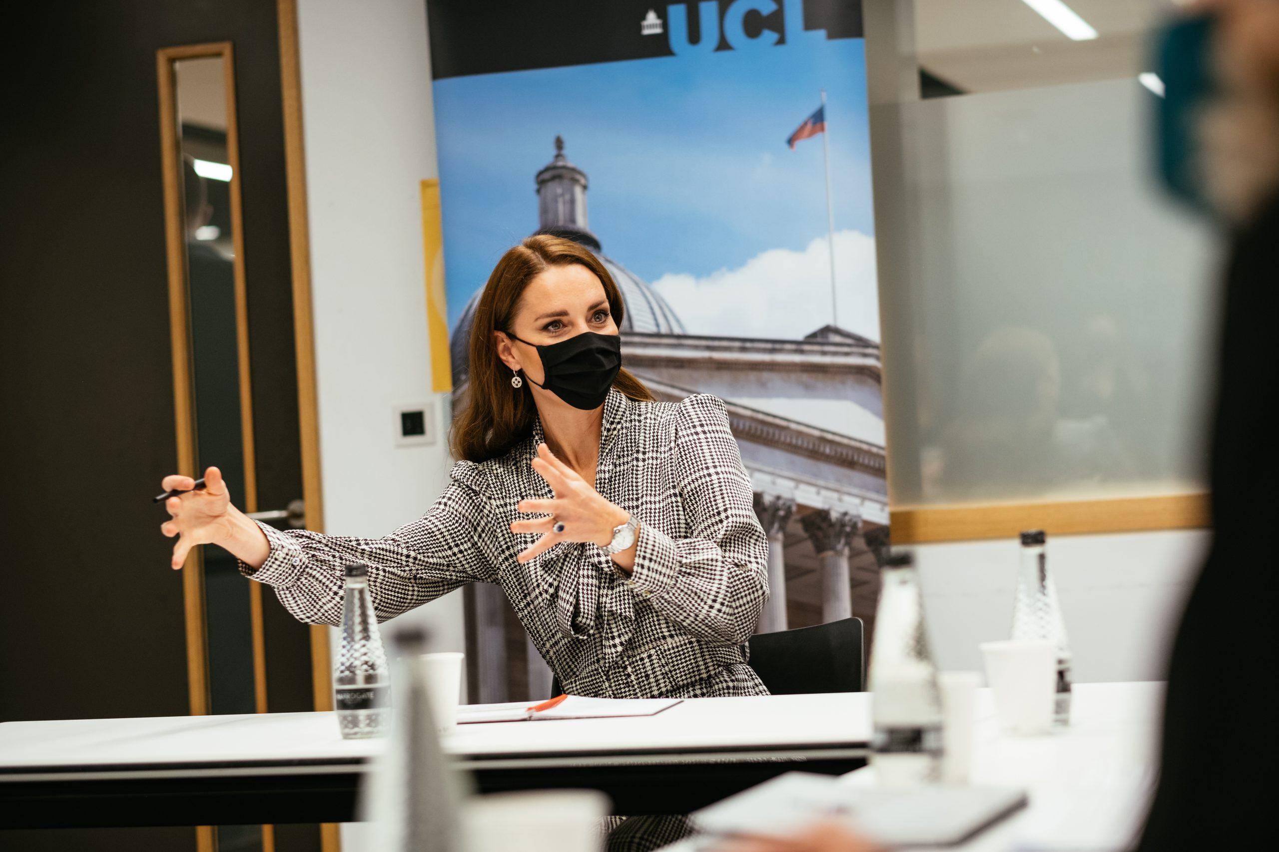 The Duchess of Cambridge explaining something in front of a UCL banner